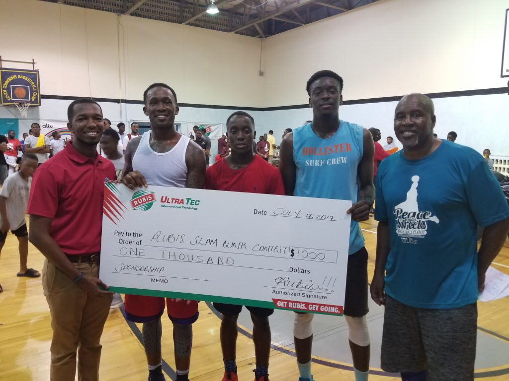 RUBiS Bahamas Limited Marketing Programs Coordinator O'Niel Bain presents $1000 RUBiS cheque to the winner of the RUBiS Slam Dunk contest.
